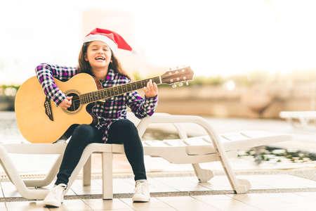 若い混合レースの女の子、ギターを弾き歌とクリスマスのスイミング プールで楽しく笑ってサンタ帽子、音楽や幸福の概念、コピー スペースが付い