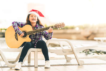 Young mixed race girl playing guitar, singing and smiling joyfully by swimming pool, with christmas santa hat, music or happiness concept, sunset warm light tone effect, with copy space 写真素材