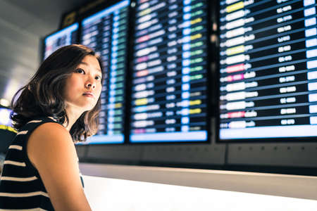 Beautiful Asian woman traveler at flight information screen in an airport, travel or time concept Foto de archivo