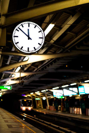 Train platform with clock at almost midnight, time or transportation abstract concept Stock Photo