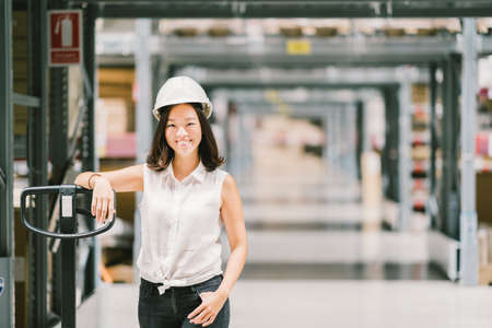 Beautiful young Asian engineer or technician woman smiling, warehouse or factory blur background, industry or logistic concept, with copy space