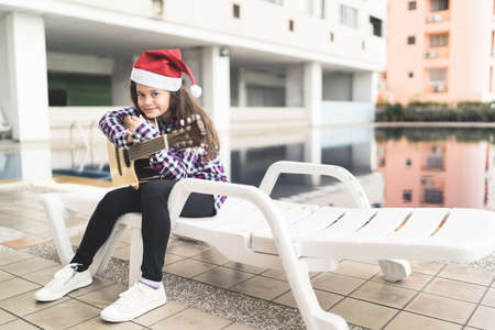 Young mixed race girl with guitar, sitting by swimming pool, with christmas santa hat, music concept