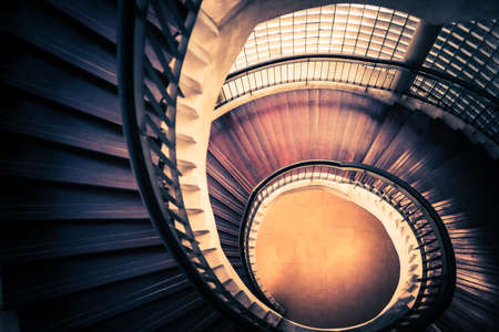 Staircase in spiral or swirl shape, fibonacci golden ratio composition, abstract or architecture concept, dark vintage mysterious tone