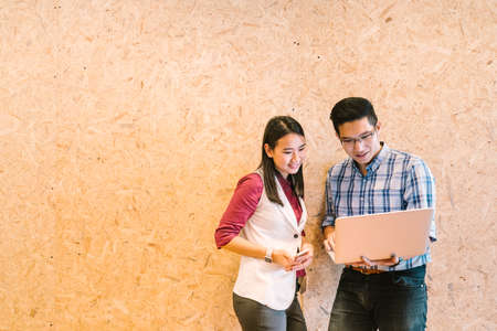 Young Asian couple or coworker working on laptop, casual business colleagues or information technology concept, with copy space