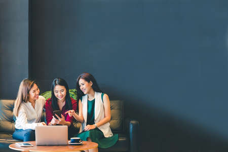 Three beautiful Asian girls using smartphone and laptop, chatting on sofa at cafe with copy space, modern lifestyle with gadget technology or working woman on casual business concept