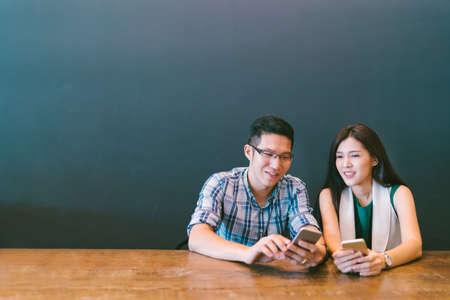복사 공간 카페에서 스마트 폰을 사용하는 젊은 아시아 부부 또는 동료, 가젯 기술 또는 캐주얼 비즈니스 개념과 현대적인 라이프 스타일, 스톡 콘텐츠