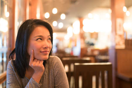 Tanned Asian girl thinking and looking upward to copy space, wondering menu to order for dinner, restaurant advertising concept Stock Photo