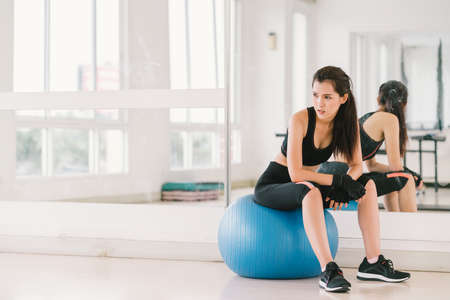 Young and determined sexy Asian girl on fitness ball at gym with copy space, sport and healthy lifestyle concept