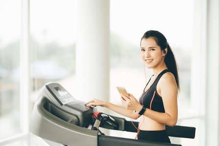 Cute Asian girl on treadmill at gym listening to music on smartphone via sport earphone, healthy fitness lifestyle concept with copy space