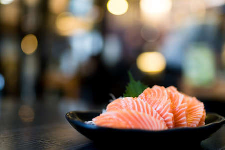 Sliced salmon sashimi on wooden table, Japanese food delicious menu, bokeh blurred background with copy space
