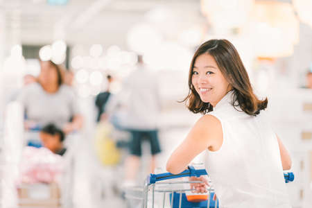 cart: Smiling Asian woman with shopping cart or trolley at department store or shopping mall, happy lifestyle or shopaholic concept, blur bokeh background with crowd and copy space Stock Photo