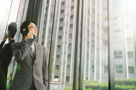 携帯電話、ビジネスやコミュニケーションの技術概念を用いたレンズ フレアの効果とコピーの空間アジア ビジネスの男性