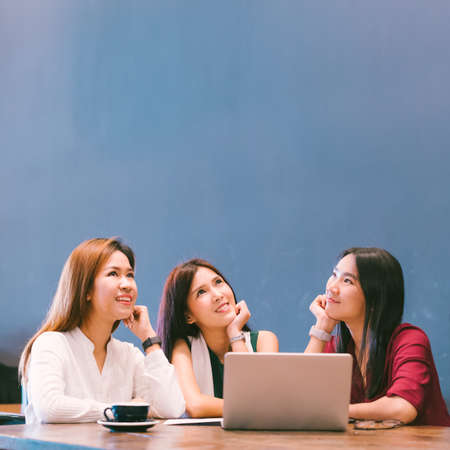 Three beautiful Asian girls looking upward to copy space while working at cafe, modern lifestyle with gadget technology or working woman on casual business concept Standard-Bild