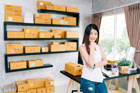 Young Asian small business owner at home office, online marketing packaging and delivery scene, startup SME entrepreneur or freelance woman working at home concept 写真素材