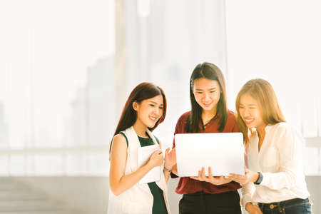 Three beautiful Asian girls on casual business meeting with laptop notebook and digital tablet at sunset, modern lifestyle with gadget technology or working women concept, with copy space