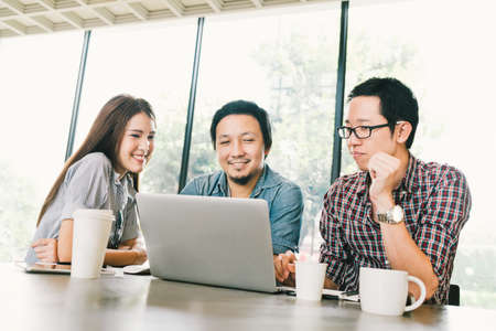Group of young Asian business colleagues or college students using laptop in team casual discussion, startup project meeting or happy teamwork brainstorm concept, at coffee shop or modern office