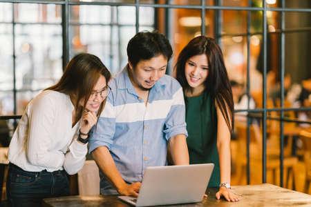 Groep van jonge Aziatische collega's in team informele discussie, startup project zakelijke bijeenkomst of gelukkig teamwork brainstorm concept, met een kopie ruimte, diepte van het veld effect, concentreren op de man