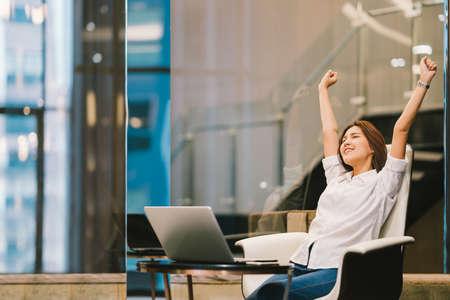아름 다운 아시아 여자 축 하 노트북, 손 스트레칭 또는 작업 성공 포즈, 교육 또는 기술 또는 시작 비즈니스 개념, 현대 사무실 또는 복사 공간이 거실