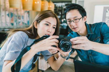 若いアジアのカップル、近代的なガジェットの技術コンセプトのコーヒー ショップで一緒にミラーレス デジタル カメラの使い方を学ぶ少女、電界