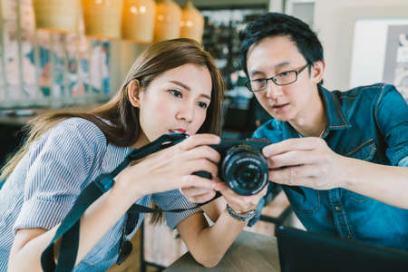 Young Asian couple learning to use mirrorless digital camera together at coffee shop, modern gadget technology concept, focus on the girl, depth of field effect Фото со стока