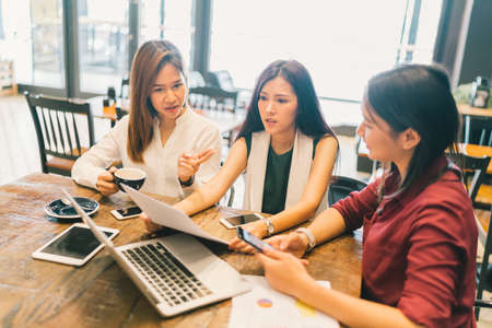 Group of young Asian women or college students in serious business meeting or project brainstorm discussion at coffee shop. With laptop computer, digital tablet, and smartphone. Startup or teamwork concept. Banque d'images