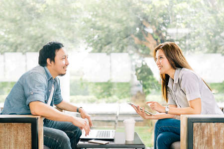 Young Asian couple or coworker talking at coffee shop or modern office, garden background. With laptop notebook, smartphone and digital tablet. Modern lifestyle with computer gadget technology concept Standard-Bild