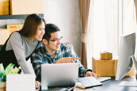 Młoda para azjatyckich uruchamiania rodzinnego biznesu, opakowania do marketingu online i scenę dostawy. Przedsiębiorca MŚP, partner biznesowy lub niezależna praca w domu koncepcji