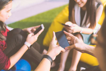 Group of three young people using smartphones together, modern lifestyle or communication technology gadget concept, depth of field effect