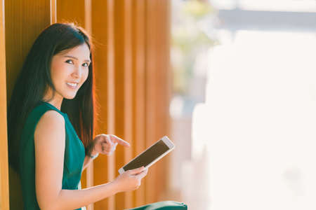 vdo: Asian businesswoman or college student using and pointing at digital tablet during sunset, at modern office or library. Business communication, gadget technology, or education concept with copy space