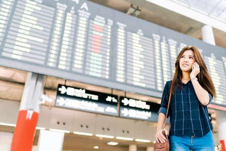 空港でフライト情報ボードで携帯電話上でアジアの女性の美しい旅行休暇休暇旅行やコミュニケーション コンセプト