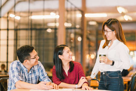 Young Asian college students or coworkers social meeting at coffee shop, diverse group. Casual business, freelance work at cafe, or education concept Standard-Bild