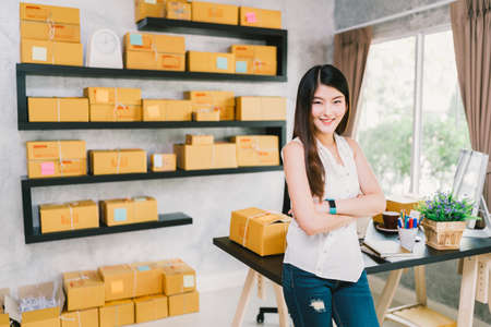 Young Asian small business owner at home office, online marketing packaging and delivery scene, startup SME entrepreneur or freelance woman working at home concept Standard-Bild