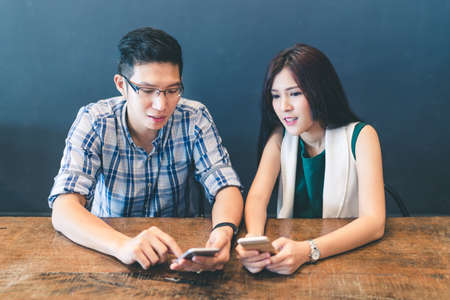 Young Asian couple, college students, or coworkers using smartphone together at cafe, modern lifestyle with gadget technology or love and relationship concept