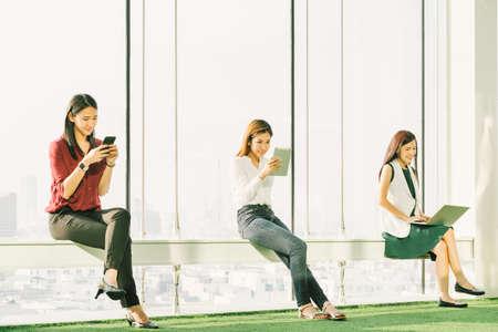 Drie Aziatische meisjes met behulp van smartphone digitale tablet en laptop computer in moderne kantoor bij zonsondergang. Moderne levensstijl, informatietechnologie, internet gadget of draadloos online communicatie concept