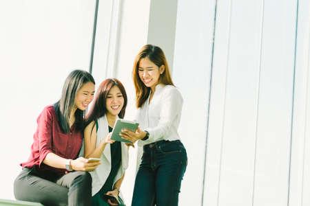 Drie mooie Aziatische meisjes die digitale tablet samen gebruiken. Werkende vrouw of studenten die op kantoor met exemplaarruimte babbelen. Moderne levensstijl met gadgettechnologie of toevallig bedrijfsconcept Stockfoto