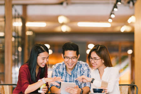 Young Asian college students or coworkers using digital tablet together at coffee shop, diverse group. Casual business, freelance work at cafe, social meeting, or education concept