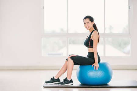Sexy young Asian girl exercise, smile on fitness ball at clean home gym, sports club. Yoga aerobic class, sport trainer, weight loss, fat burn, or healthy wellbeing lifestyle concept. With copy space Stock fotó - 83314224