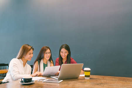 Three beautiful Asian girls using laptop in team business meeting, coworkers or college student, startup project discussion or teamwork brainstorm concept, coffee shop or modern office with copy space