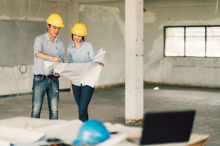 Young Asian engineers couple working on building blueprint at construction site. Civil engineering, industrial, or home renovation concept. With copy space