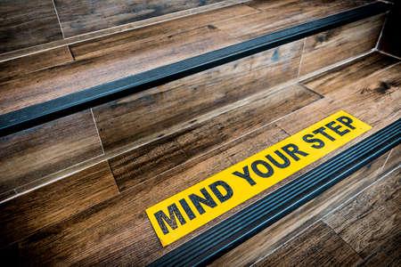 Let op dat je stapstickerbord op houten trap is geplakt. Waarschuwingen, abstract of binnen architectuur concept