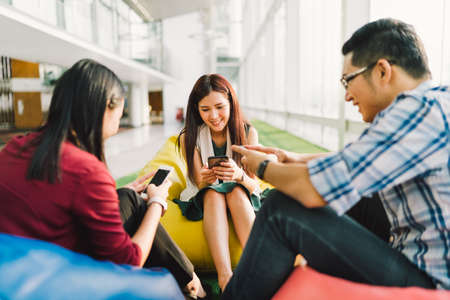 Three Asian college students or coworkers using smartphones together. Fun modern lifestyle, social network, or communication technology gadget concept, focus on middle girl, depth of field effect