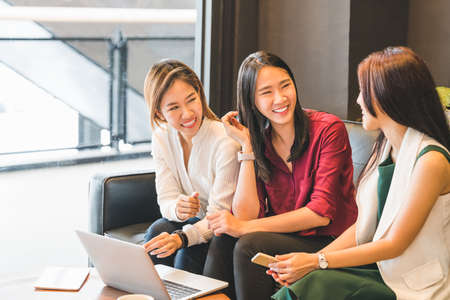 Three beautiful Asian girls chatting on sofa at cafe or coffee shop together. Gossip talks, Casual lifestyle with gadget technology, startup SME, college students or working business woman concept 스톡 콘텐츠