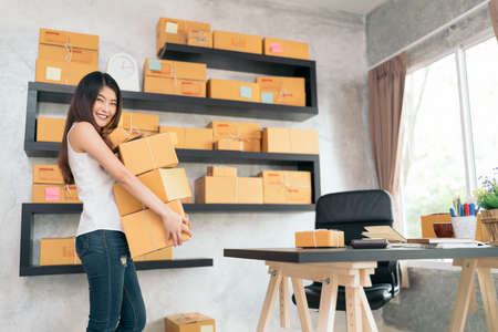 Young Asian small business owner carrying product boxes at home office, online marketing packaging and delivery scene, startup SME entrepreneur or freelance woman working at home concept
