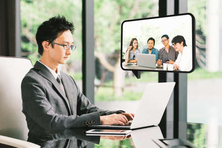 Young Asian businessman, CEO entrepreneur VDO conference call with diverse business partner group or employee. Company leader, remote live online meeting, or financial invest funding advisor concept