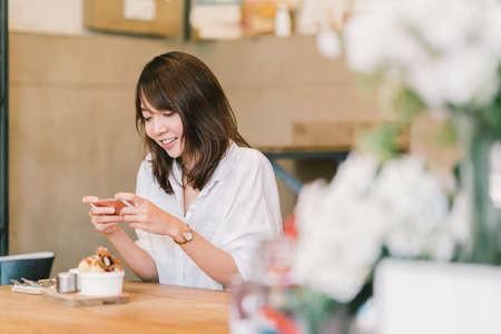Muchacha asiática hermosa que toma la foto de postres dulces en la cafetería, usando la cámara del smartphone, fijando en medios sociales. Pasatiempo de fotografía de alimentos, estilo de vida casual, concepto de hábito de red social moderna Foto de archivo - 83622674