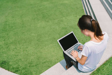 Asian college student or freelance woman using laptop on stairs in university campus or modern park. Information technology, education, or casual business concept. Copy space on green grass yard
