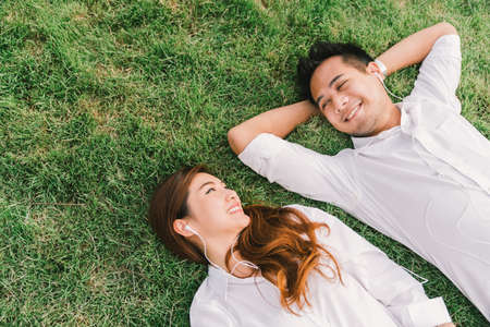 Young Asian lovely couple or college students lying down on the grass together, listening to music, top view with copy space. Love, relationship, wedding, or relaxing casual lifestyle concept 免版税图像