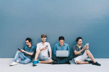 Grupo multiétnico de cuatro hombres que usan el smartphone, computadora portátil, tableta digital junto con el espacio de la copia en la pared azul. Estilo de vida con gadget de tecnología de la información, educación o concepto de red social Foto de archivo