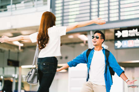 Asian girl picking up her boyfriend at airport's arrival gate, welcomes back home from studying or working abroad. Young couple love and hug, honeymoon, or traveling concept