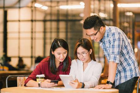 cafe internet: Jóvenes estudiantes universitarios de Asia o compañeros de trabajo utilizando tableta digital y teléfono inteligente juntos en cafetería, grupo diverso. Negocios ocasionales, trabajo freelance en el café, reunión social, o concepto de la educación Foto de archivo